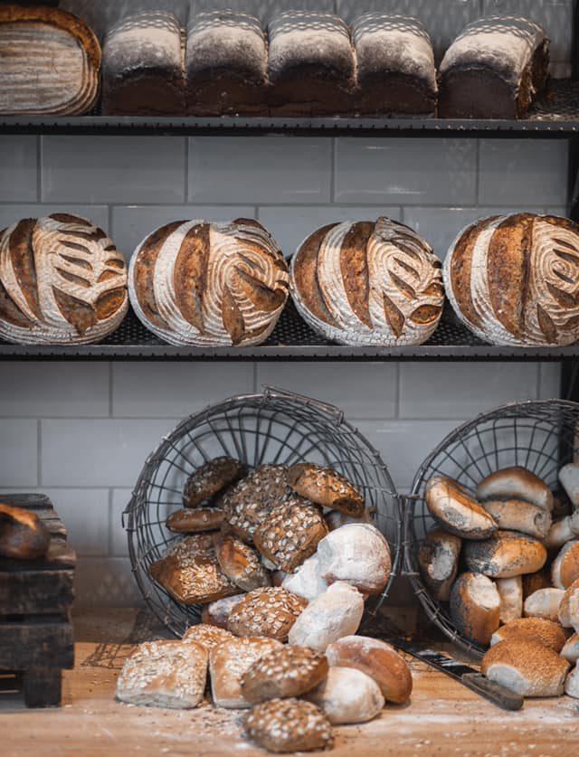 nybakade bröd i olika storlekar och former