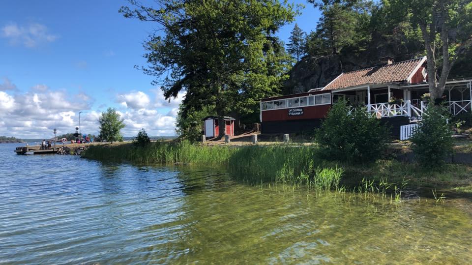 rött hus med vita knutar nära vattnet och grönska
