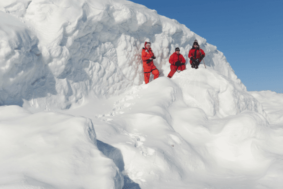 tre personer ute i snön