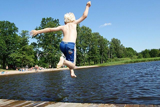 Barn som hoppar i vattnet från brygga i Värmdö