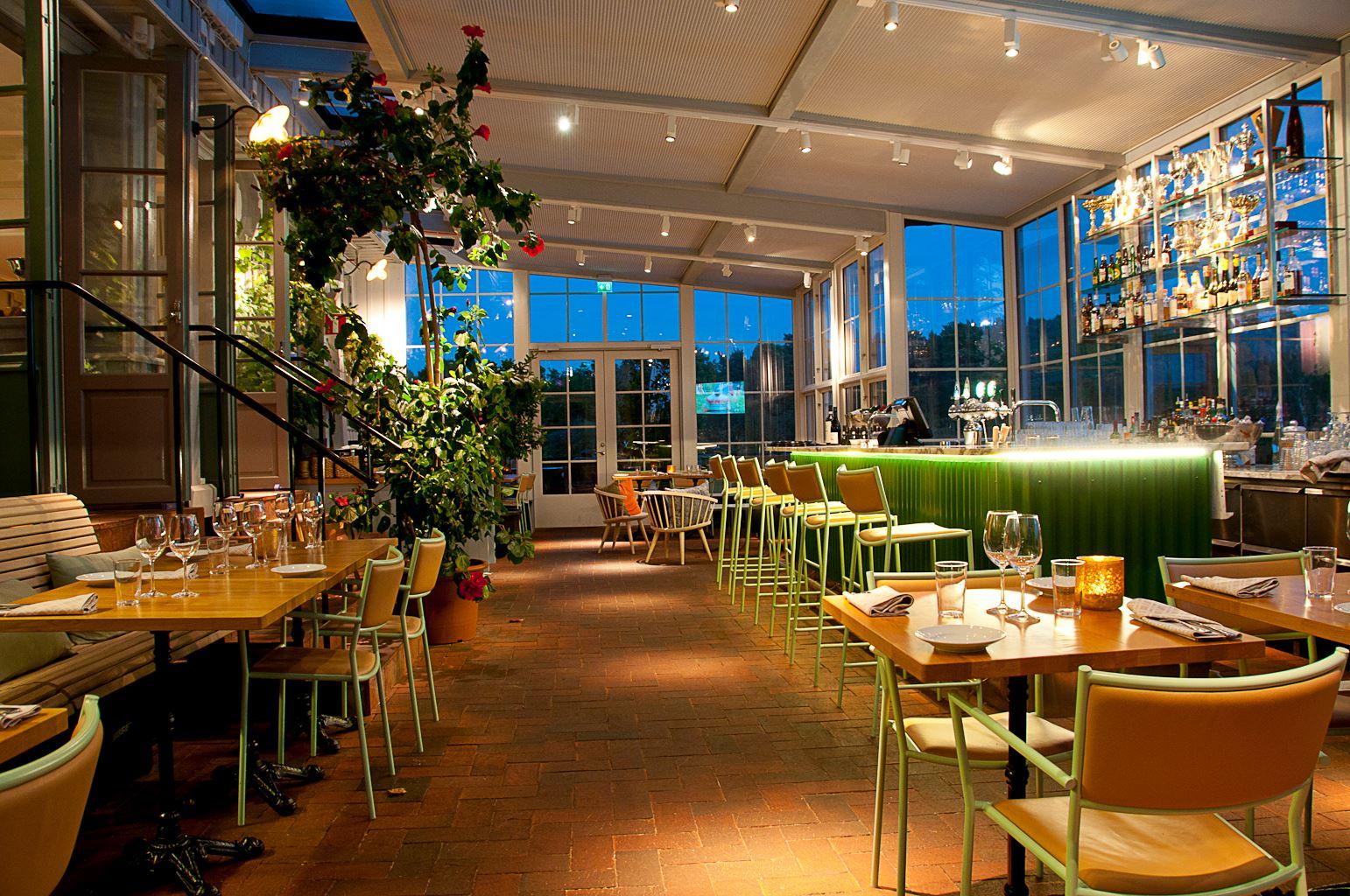 mysig restaurang med trägolv och stora fönsterrutor