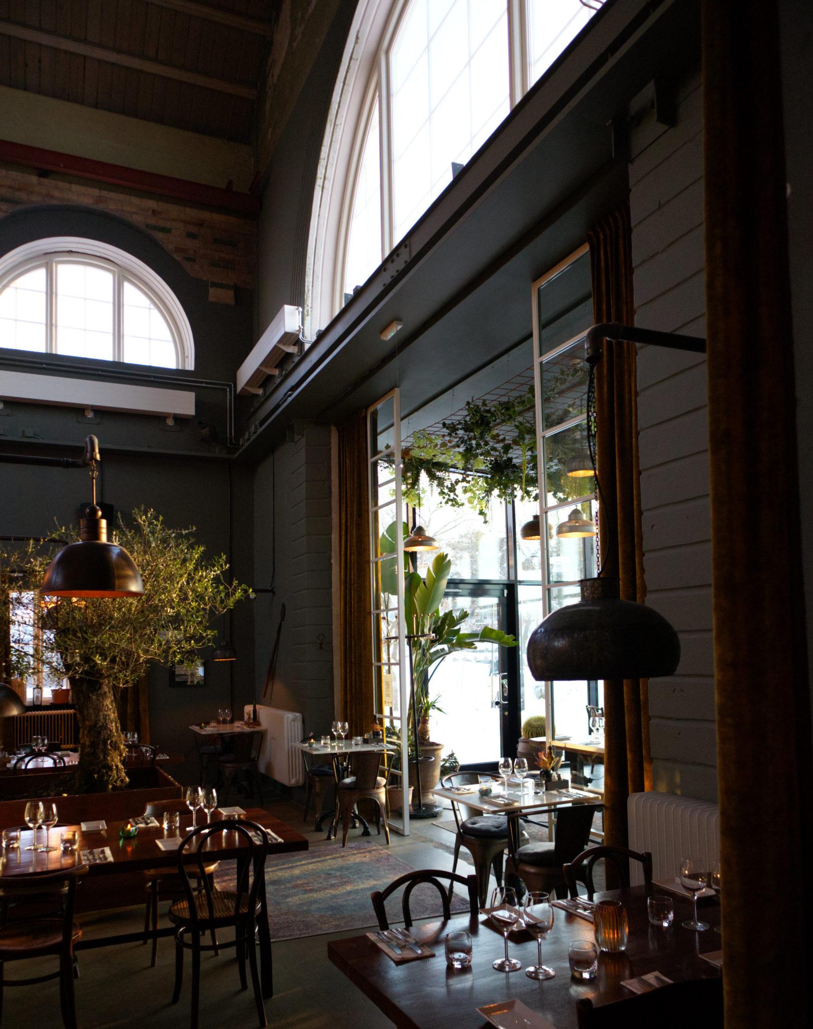 Restaurang med bord i en rustik lokal med högt i tak